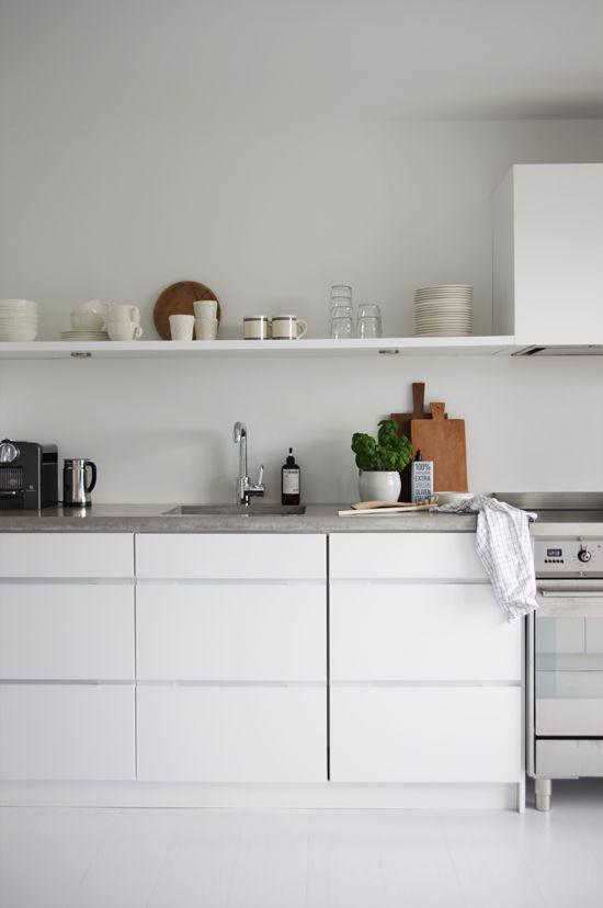 je een strakke witte keuken met betonnen keukenblad het servies ...