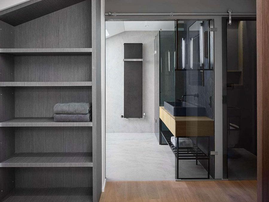 Middels een luxe glazen schuifdeur heb je toegang tot deze stoere badkamer!