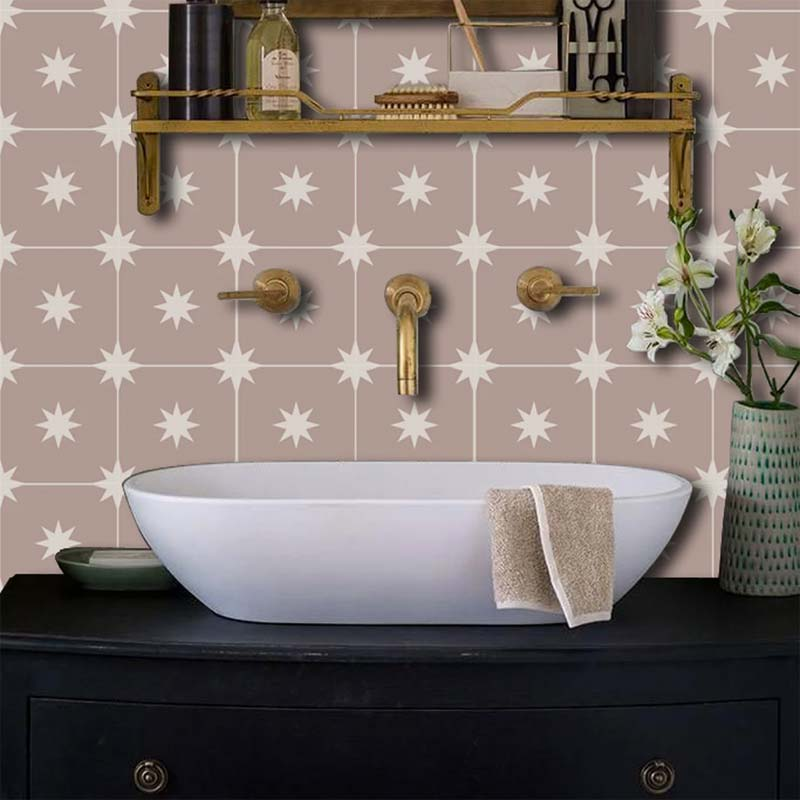 De tegels aan de wastafel wand is betegeld met de leuke oudroze Quadrostyle Starry Night tegelstickers.