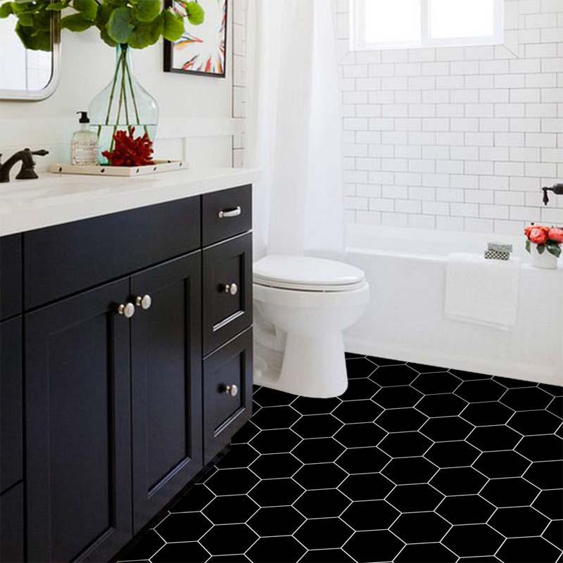 De vloertegels in deze badkamer zijn beplakt met de zwarte hexagon tegelstickers van Quadrostyle.